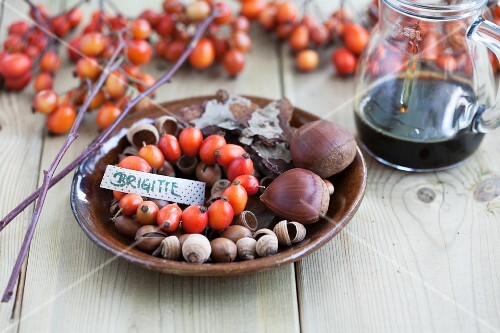 A nametag with a wreath of rosehips, chestnuts and acorns on a brown plate