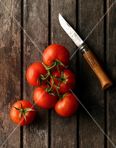 Vine tomatoes and a knife on a wooden surface