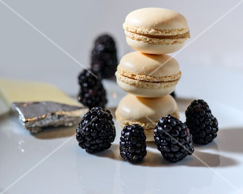 A stack of macaroons with blackberries and white chocolate