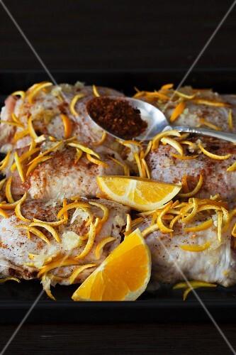 Raw chicken bits with orange zest, oranges wedges and chilli