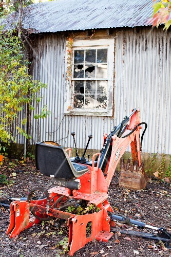 A metal shed and a red digger