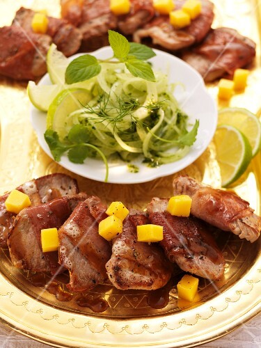 Pork fillet wrapped in ham on an onion and mint salad (India)