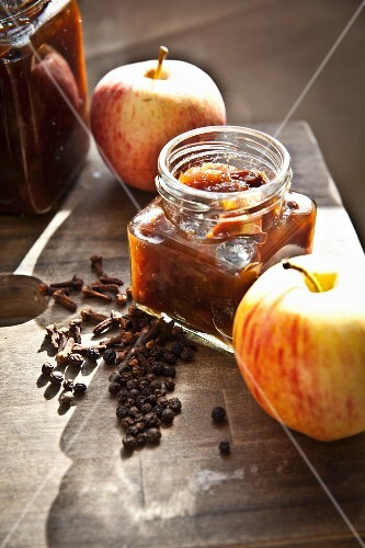 Jars of homemade apple chutney with fresh apples and spices