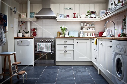 Kitchen with white furniture, fitted appliances and utensils on wall-mounted shelf