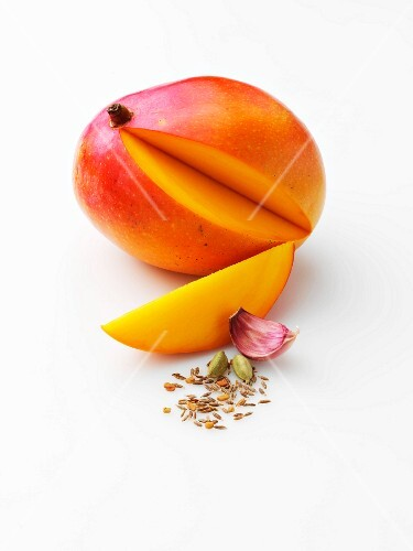A sliced mango with a garlic clove and spices