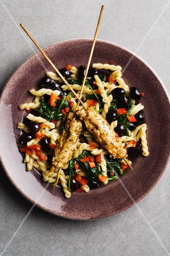 Chicken skewers on fried pasta with spinach, peppers and black olives