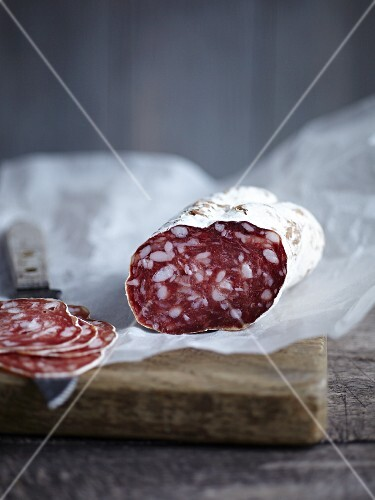 Salami, sliced, on a piece of paper