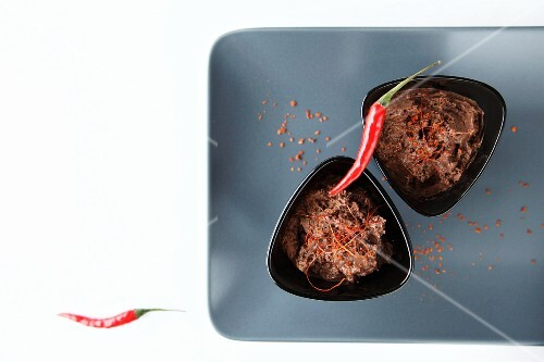 Two portions of chocolate and chilli mousse with chilli peppers and chilli threads