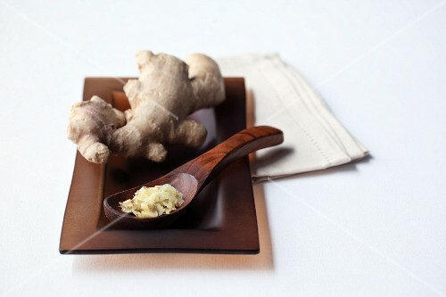 Grated ginger on a wooden spoon in front of a ginger root