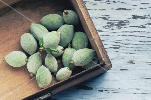 Unripe almonds in wooden crate