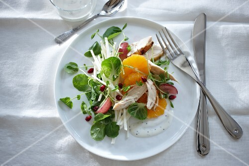 Watercress and orange salad with pomegranate seeds and chicken breast