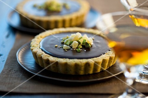 Ganache tart with a pistachio crust and a cocktail in the foreground