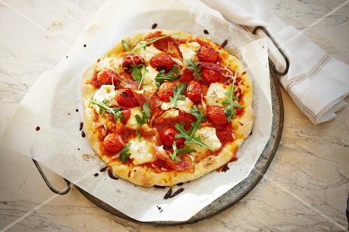 A pizza topped with prosciutto, mozzarella and rocket