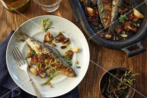 Roasted sardines with vegetables and herbs in an iron pan and on a plate