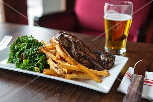 Dry-aged New York strip steak with fries and green kale salad
