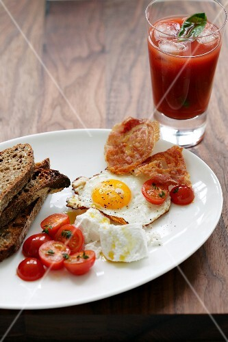 Breakfast with toast, fried egg, bacon and tomatoes