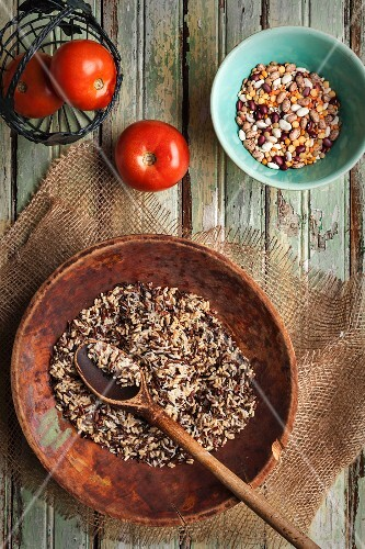 Wild rice, assorted beans and tomatoes on an old wooden table