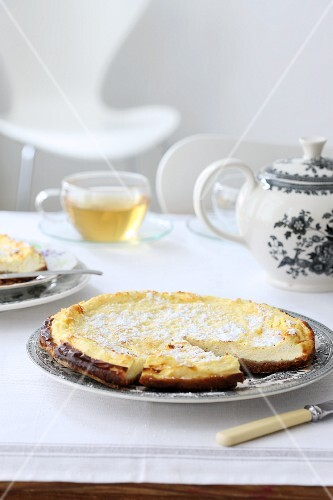 Cheesecake with icing sugar, sliced, for teatime