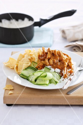 Chicken served on a bed of rice with potato crisps and a cucumber salad