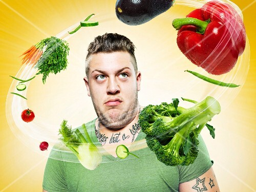 A young man surrounded by flying vegetables