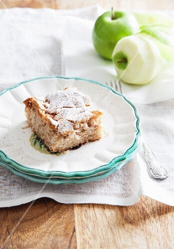A slice of apple cake dusted with icing sugar