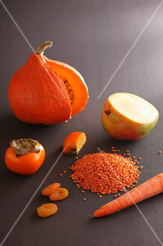 An orange pumpkin, a persimmon, a mango dried apricots, lentils and a carrot