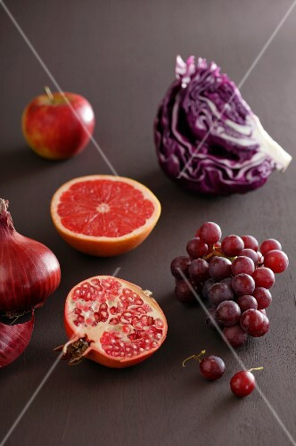 An arrangement featuring a red cabbage, grapes, a pomegranate, a grapefruit, an apple and onions