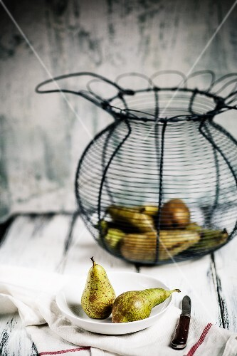 An arrangement of pears and a wire basket
