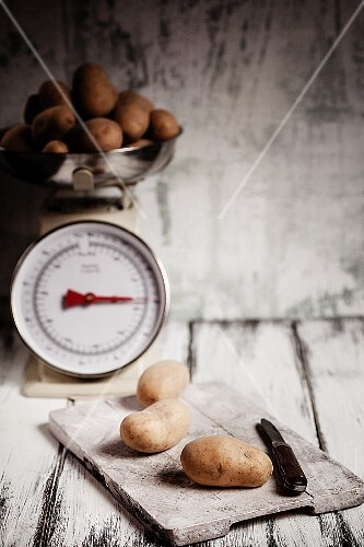 Potatoes on a chopping board and on an old pair of kitchen scales