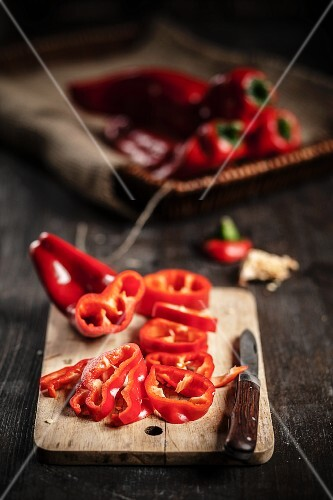 Sliced red pointed peppers on a board with a knife