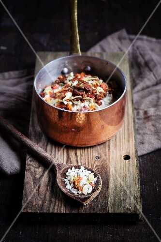 Risotto rice with a spice mixture made from dried tomatoes, herbs and garlic in a copper pot and on a wooden spoons