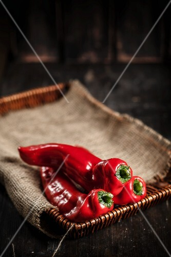 Red pointed peppers on a cork tray