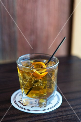 A drink with ice and orange zest