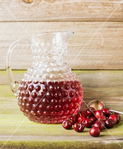 A jug of cherry juice with fresh cherries