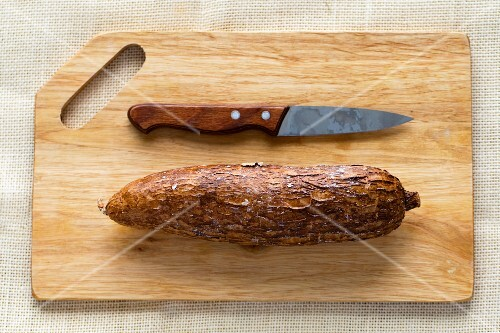 A cassava root on a chopping board with a knife