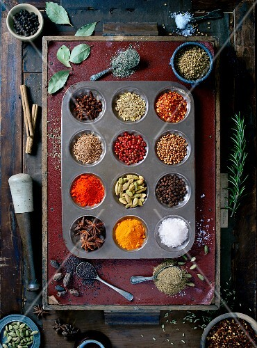 Various different spices in a muffin tin