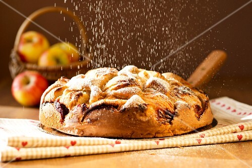 Apple cake being dusted with icing sugar