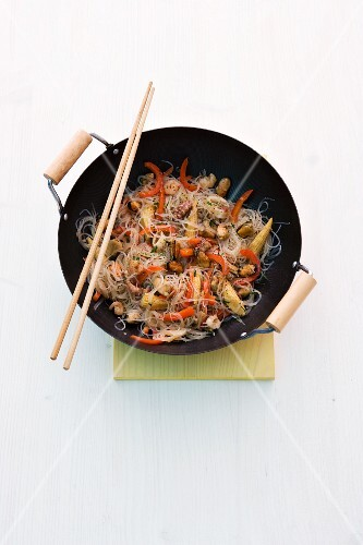 Stir-fried seafood with glass noodles in a wok