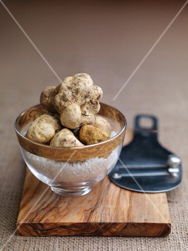 White truffles in a glass bowl on a wooden board