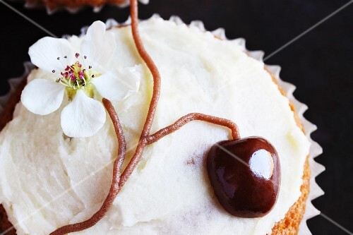 A cupcake decorated with a cherry and a cherry blossom flower