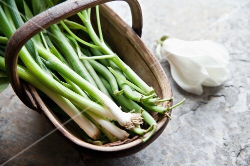 Spring onions and green beans in a wooden basket