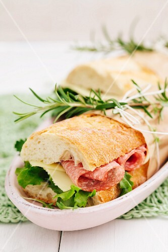 Baguette sandwiches with lettuce, sliced cheese and salami