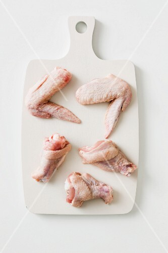 Chicken wings and legs on a chopping board