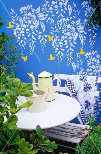 Wandfresko mit Kolibris und Wysteria auf einer blau bemalten Gartenmauer, davor ein weißer Tisch und Stuhl mit Kaffeekanne