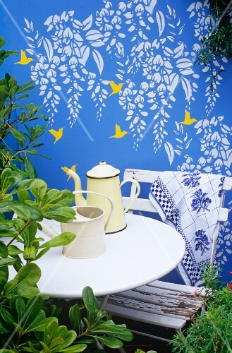 Fresco of humming birds and wisteria on blue-painted garden wall behind white table, chair and coffee pot