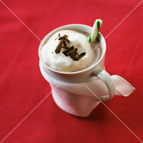 Hot chocolate garnished with a candy cane and grated chocolate