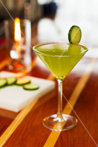 A cocktail garnished with a slice of cucumber
