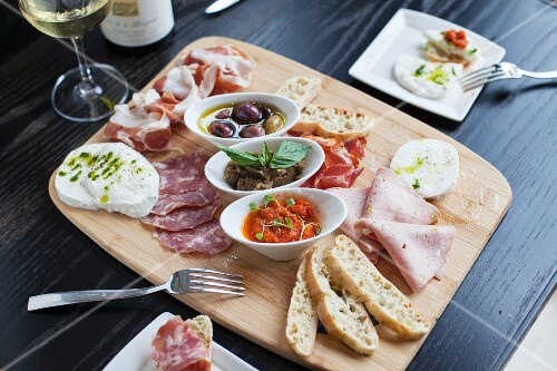 An antipasti platter with salami, Parma ham, mozzarella, spreads, olives and white bread