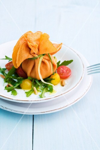 Stuffed crepes parcels on a rocket and tomato salad