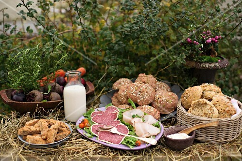 An autumnal buffet with rolls, sausages and vegetables in a garden